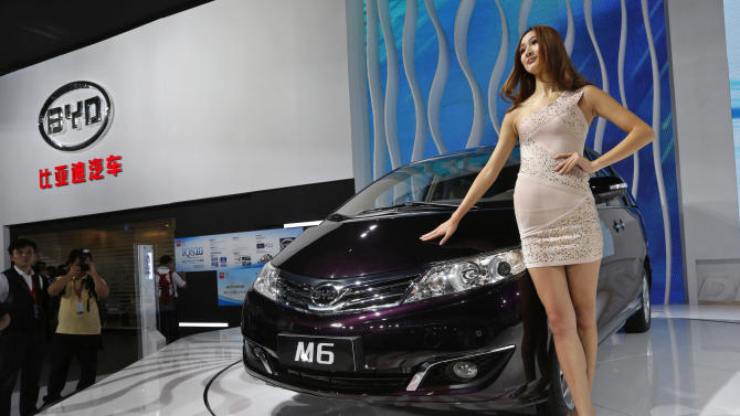A model poses with a BYD (Build Your Dream) M6 minivan at the Chinese auto maker's booth during the Guangzhou Auto Show in China's southern city of Guangzhou Thursday, Nov. 22, 2012. (AP Photo/Vincent Yu)