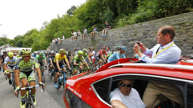 Tour de France director Christian Prudhomme takes a picture with his mobile phone as former Belgian cycling champion Eddy Merckx looks on at the start of the 4th stage of the 102nd Tour de France cycling race from Seraing to Cambrai