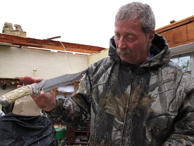Wayne Osmus holds up an ivory-handled knife that he salvaged from the wrecked of his home in Moore, Okla., on Tuesday, May 21, 2013. Osmus' family was forced to hide in a closet Monday when winds prev