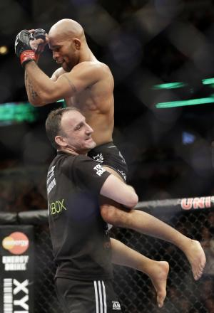 Demetrious Johnson, top, celebrates with his crew member after he finished the fifth round of UFC World Flyweight Championship on FOX 6 against John Dodson at the United Center in Chicago, Saturday, Jan. 26, 2013. Demetrious Johnson won. (AP Photo/Nam Y. Huh)