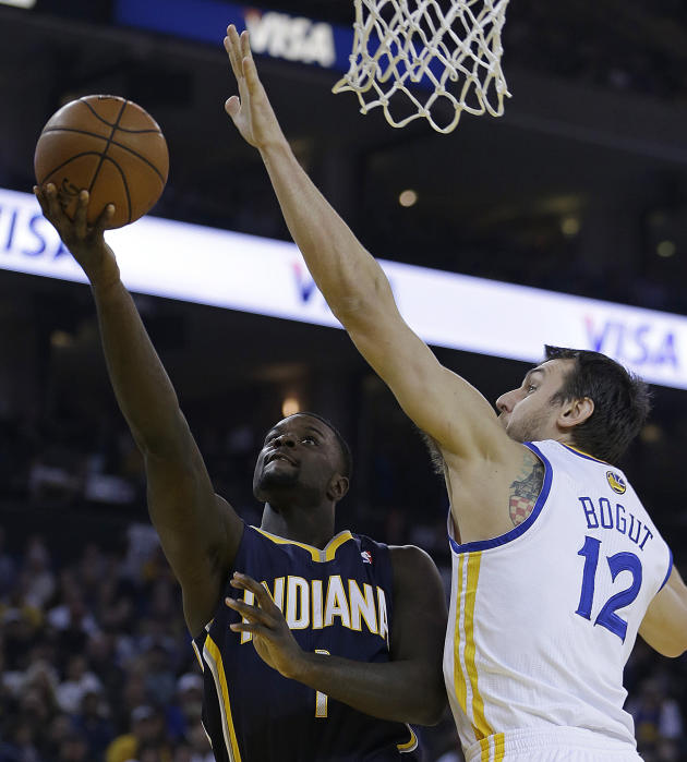 Indiana Pacers' Lance Stephenson, left, lays up a shot against Golden State Warriors' Andrew Bogut (12) during the first half of an NBA basketball game, Monday, Jan. 20, 2014, in Oakland, Cali
