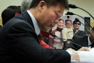 A photo of Chinese human rights lawyer Chen Guangcheng and his family is on display as Chinese dissident and president of ChinaAid Bob Fu prepares his testmony during a hearing before the Congressional-Executive Commission on China on Capitol Hill in Washington, DC