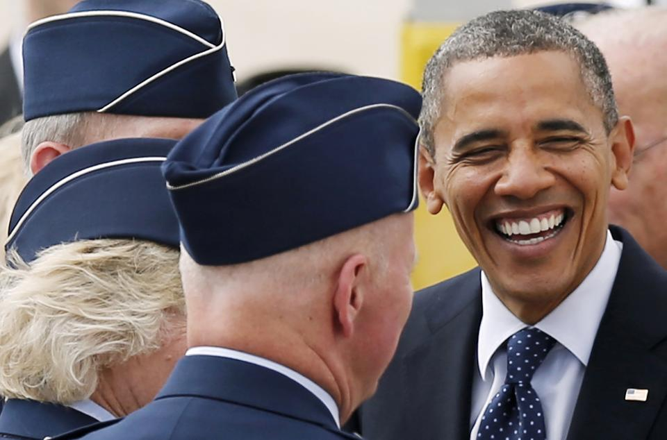 President Barack Obama shares a laugh with service members upon his arrival at Pease Air National Guard Base in Portsmouth, N.H., Friday, Sept. 7, 2012. (AP Photo/Winslow Townson)