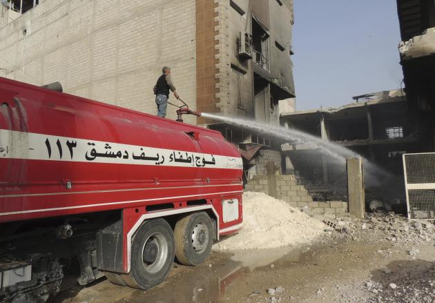 A firefighter extinguishes fire caused by what activists said was an air strike by forces loyal to Syria's President Bashar al-Assad in Arbeen, in the eastern Damascus suburb of Ghouta