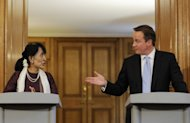 British Prime Minister David Cameron (right) gestures toward Myanmar democracy icon Aung San Suu Kyi during a joint press conference at 10 Downing Street in London. Suu Kyi urged the world to help Myanmar complete its journey towards democracy as she became the first foreign woman to address both houses of Britain's parliament