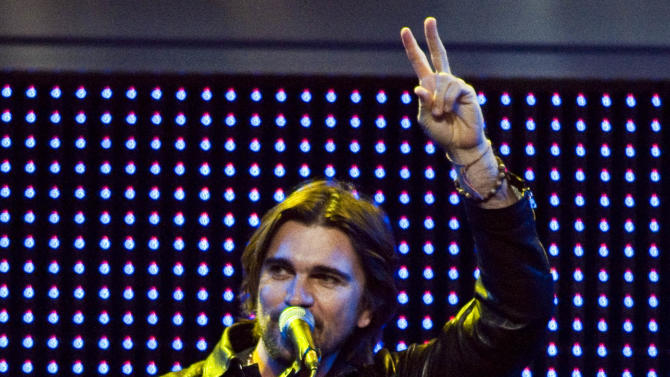 Latin Grammy award winning artist Juanes gestures to the crowd during a performance at the Walmart Stores Inc. shareholders' meeting in Fayetteville, Ark., Friday, June 1, 2012. (AP Photo/April L. Brown)