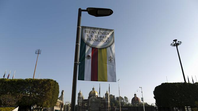 A banner is seen in front of the Basilica of Guadalupe while believers visit it, ahead of the upcoming visit of Pope Francis to Mexico City
