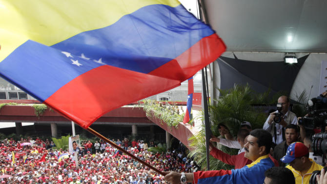 Venezuela's acting President Nicolas Maduro waves a Venezuelan flag over supporters after registering his candidacy for president to replace late President Hugo Chavez at the national electoral council in Caracas, Venezuela, Monday, March 11, 2013.  Elections were announced to take place on April 14, after the death of Chavez on March 5. (AP Photo/Ariana Cubillos)