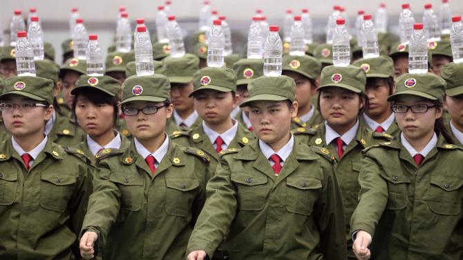 Students in military uniforms balance bottles of water on their heads as they practice goose-stepping marching during a military training session at a college in Zhengzhou