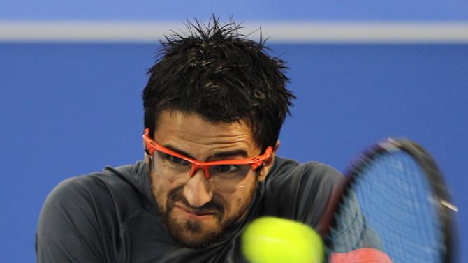 Serbia's Janko Tipsarevic returns the ball to Andy Murray from Britain during the first day of Mubadala Tennis Championship in Abu Dhabi, United Arab Emirates, Thursday, Dec. 27, 2012. (AP Photo/Kamran Jebreili)