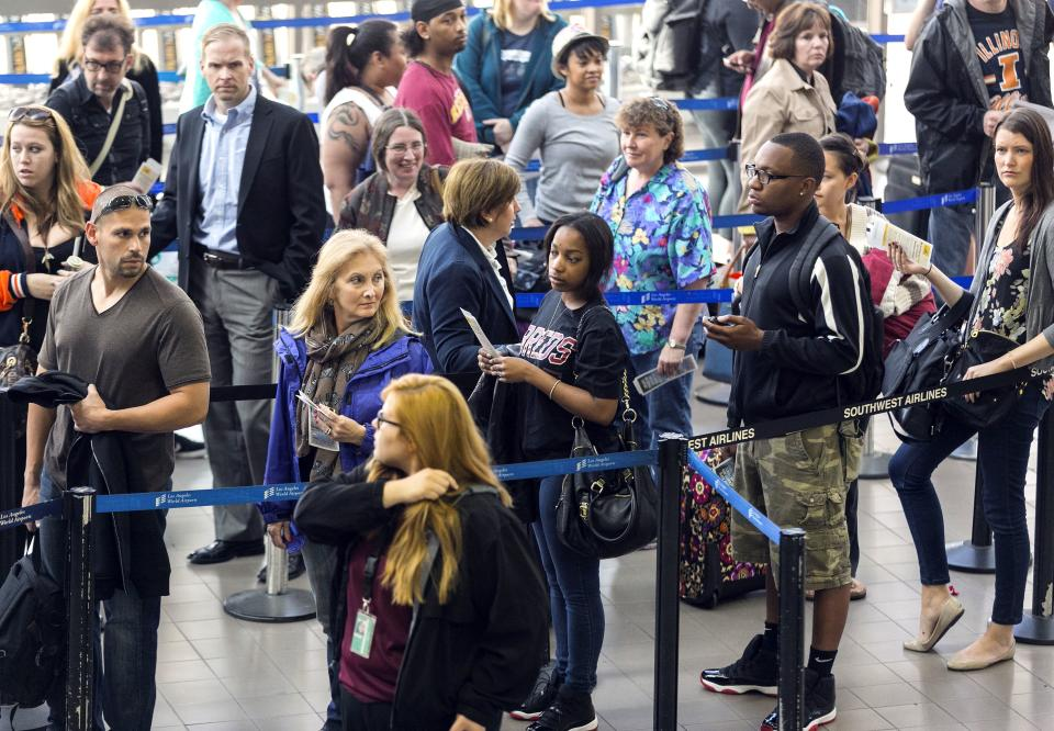 Travelers stand in line at Los Angeles International airport in Los Angeles Monday, April 22, 2013. Flight delays piled up Monday as thousands of air traffic controllers were forced to take an unpaid day off because of federal budget cuts. (AP Photo/Damian Dovarganes)