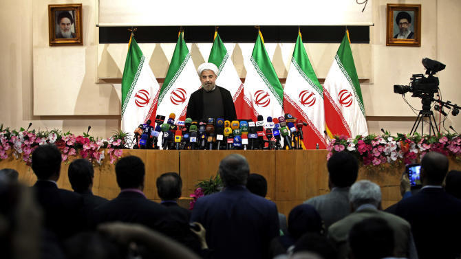 """Iranian newly elected President Hasan Rowhani, listens to the Iranian national anthem, before beginning a press conference, in Tehran, Iran, Monday, June 17, 2013. Rowhani showcases his reformist image by promising a """"path of moderation,"""" the easing of nuclear tensions and steps to narrow the huge divide with the United States. He also make clear where he won't go, saying he opposes any halt to uranium enrichment, at the heart of the nuclear standoff. (AP Photo/Ebrahim Noroozi)"""