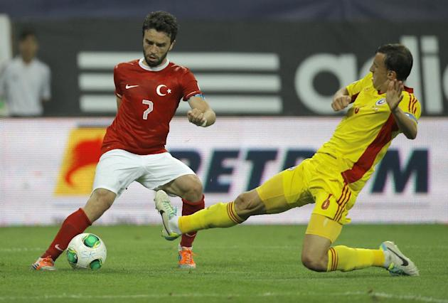 Turkey's Gokhan Gonul, left, challenges for the ball with Romania's Vlad Chiriches during a World Cup Group D qualifying soccer match between Romania and Turkey at the National Arena stadium in Buchar
