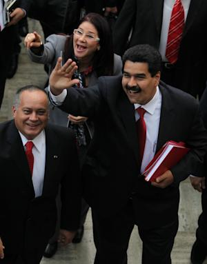 Venezuela Vice President Nicolas Maduro, right, Diosdado Cabello, left, National Assembly president and Cilia Flores, center back, attorney general, greet supporters upon their arrival for the state of the nation address in Caracas, Venezuela, Tuesday, Jan. 15, 2013. Maduro took the place of the country's ailing President Hugo Chavez Tuesday by delivering a short state-of-the-nation address amid legal debate about his legitimacy. (AP Photo/Fernando Llano)