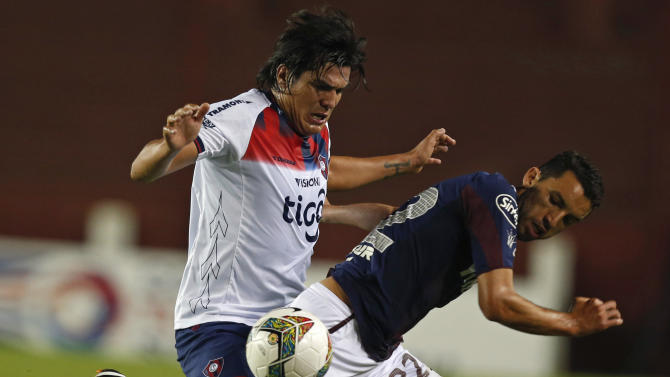 Ortiz of Argentina's Lanus is challenged by Oviedo of Paraguay's Cerro Porteno during their Copa Sudamericana soccer match in Buenos Aires