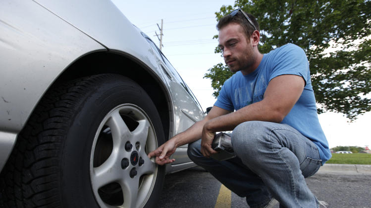 In this Aug. 11, 2011 photo, Jeff Swanson, 25, looks at the rear rotors on his 10-year-old Pontiac Grand Prix in Sterling Heights, Mich. Swanson, who was in the market for a new car just weeks ago, decided to keep his 10-year-old Pontiac Grand Prix for at least another year. Gyrations in stocks and talk of a weakening economy rattled Swanson's confidence about taking on another payment, even though his new job running a home for mentally disabled people seems to be secure. (AP Photo/Paul Sancya)