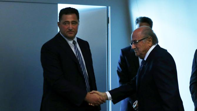 FIFA President Blatter shakes hand with Scala Chairman of the FIFA's Audit and Compliance Committee after his statement during a news conference at the FIFA headquarters in Zurich