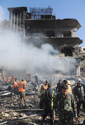 """In this photo released by the Syrian official news agency SANA, Syrian army soldiers and security officers inspect the blast area in front of a damaged building of the air intelligence forces, which was attacked by one of two explosions, in Damascus, Syria, on Saturday, March 17, 2012. Two """"terrorist explosions"""" struck security targets in the Syrian capital Saturday morning, killing a number of civilians and security forces, the country's state news agency said. The report said preliminary reports indicated they blasts were caused by car bombs that hit the aviation intelligence department and the criminal security department. (AP Photo/SANA)"""