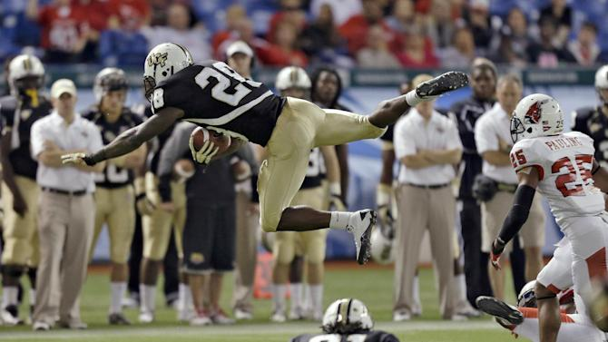 Central Florida running back Latavius Murray (28) is sent flying on a hit by Ball State safety Chris Pauling (25) during the first quarter of the Beef 'O' Brady's Bowl NCAA college football game Friday, Dec. 21, 2012, in St Petersburg, Fla. (AP Photo/Chris O'Meara)