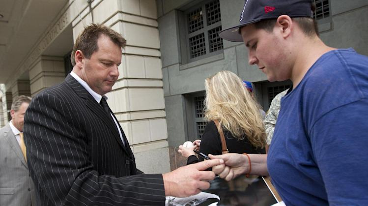 Former Major League Baseball pitcher Roger Clemens, left, signs autographs as he leave federal court in Washington, Monday, June 5, 2012, after court ended for the day in his perjury trial.  (AP Photo/Manuel Balce Ceneta)