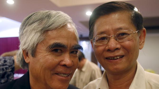Vietnam War photographer Nick Ut poses for a photo with war veteran Nguyen Huy Hoang during a reception for Vietnam War journalists and veterans in southern Ho Chi Minh City