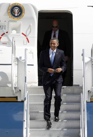 President Barack Obama jogs down the stairs of Air Force One upon his arrival at Miami International Airport, Thursday, Feb. 23, 2012 in Miami. (AP Photo/Wilfredo Lee)