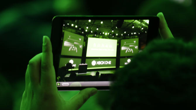 An audience member photographs the stage at the unveiling of Microsoft Corp.'s next-generation Xbox One entertainment and gaming console system, Tuesday, May 21, 2013, in Redmond, Wash. (AP Photo/Ted S. Warren)