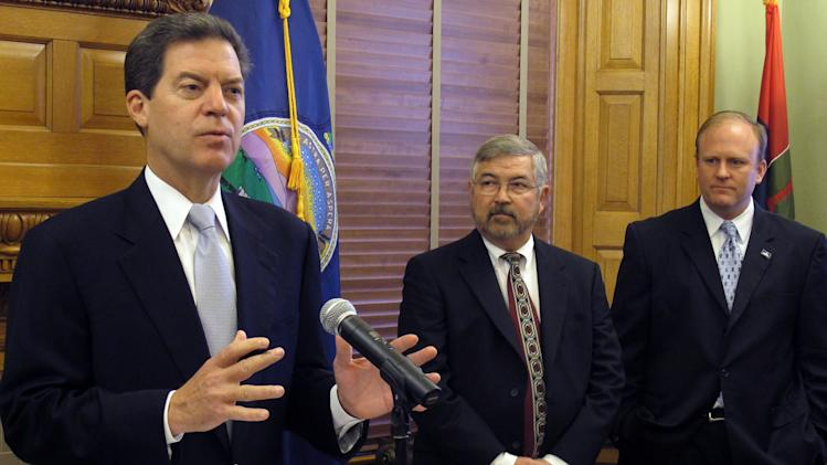 Kansas Gov. Sam Brownback, left, introduces Jim Mann, center, as the new chief information technology officer for the executive branch of state government, Monday, Nov. 7, 2011, at the Statehouse in Topeka, Kan. Standing to the right of Mann, a St. Augustine, Fla., consultant with experience in managing business IT systems, is Kansas state Rep. Mike Burgess, a Topeka Republican and chairman of the House Government Efficiency Committee. (AP Photo/John Hanna)