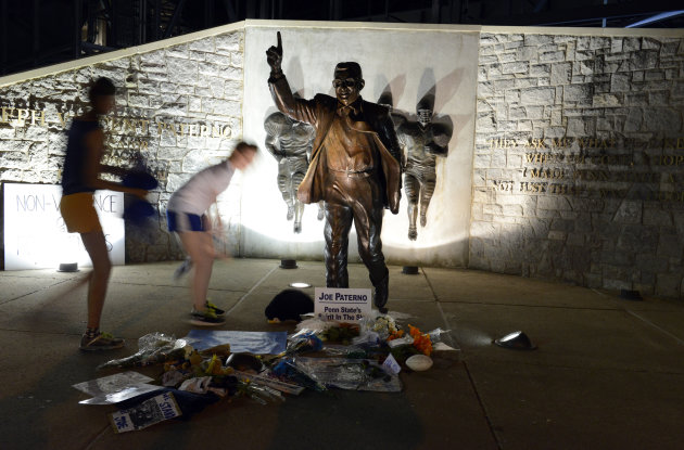 July 22 People visit the Joe Paterno statue early Sunday July 22, 2012. in State College, Pa. The famed statue of Paterno was taken down from outside the Penn State football stadium Sunday morning, el