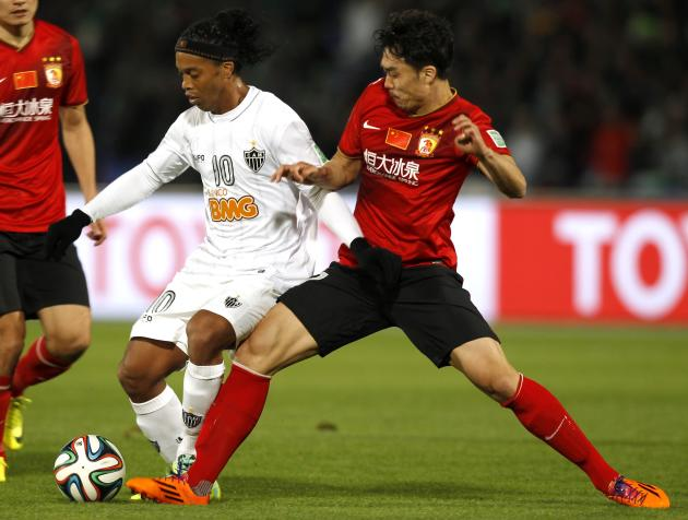 Ronaldinho of Brazil's Atletico Mineiro fights for the ball with Zhao Xuri of China's Guangzhou Evergrande during their 2013 FIFA Club World Cup third place soccer match in Marrakech stadium