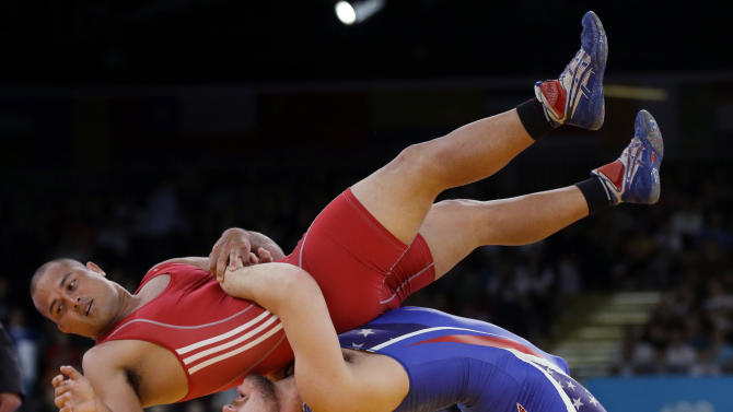 FILE - In this Monday, Aug. 6, 2012 file photo Keitani Graham of Micronesia competes against Charles Edward Betts of the United States, right, during the 84-kg Greco-Roman wrestling competition at the 2012 Summer Olympics, in London. An official familiar with the decision says IOC leaders have dropped wrestling from the program for the 2020 Olympics. In a surprise decision Tuesday Feb. 12, 2013, the official tells The Associated Press that the IOC executive board decided to retain modern pentathlon and remove wrestling instead. (AP Photo/Paul Sancya, File)
