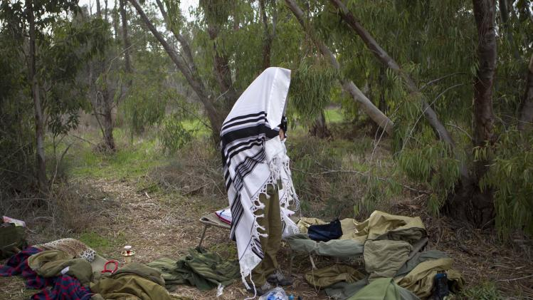 An Israeli reserve soldier wrapped in a prayer shawl offeres prayers near a 155 mm artillery position near Israel Gaza Border, southern Israel, Thursday, Nov. 22, 2012. A cease-fire agreement between Israel and the Gaza Strip's Hamas rulers took effect Wednesday night, bringing an end to eight days of the fiercest fighting in years and possibly signaling a new era of relations between the bitter enemies. (AP Photo/Ariel Schalit)
