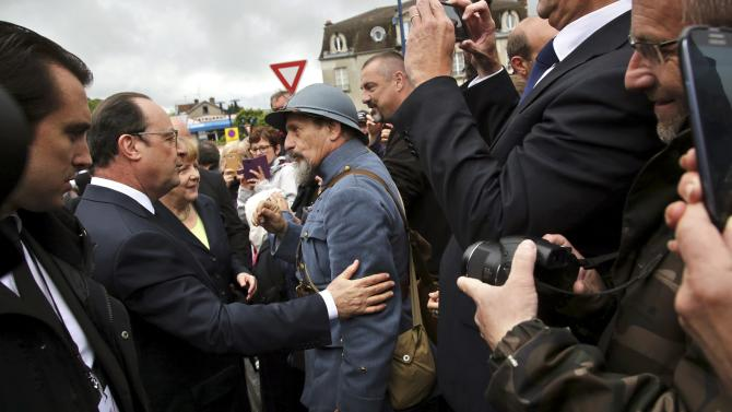 French President Francois Hollande and German Chancellor Angela Merkel walk past a history reenactor dressed as a French soldier in Verdun