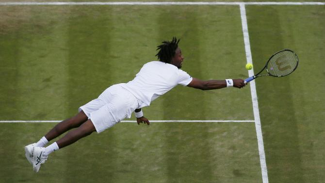Gael Monfils of France dives for the ball during his match against Gilles Simon of France at the Wimbledon Tennis Championships in London