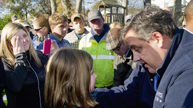 FILE - In this Nov. 5, 2012 file photo, New Jersey Gov. Chris Christie gives little 9-year-old Ginjer Doherty a pep talk outside the Port Monmouth fire station in Port Monmouth, N.J., where he visited residents and first responders a week after Superstorm Sandy devastated New Jersey. Sandy, a disaster that left more than 100 people dead, presented perhaps the biggest crisis-management test yet for three Northeastern politicians who have all been rumored to hold presidential ambitions.  At left, wiping her eye, is Ginjer's mom, Gail. (AP Photo/The Philadelphia Inquirer, Clem Murray, Pool, File)