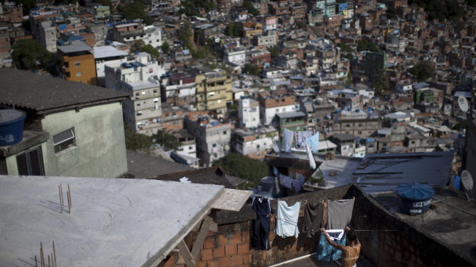 In this photo taken April 11, 2012, a woman hangs clothes at her home in Rocinha slum in Rio de Janeiro, Brazil. Setbacks in a security program meant to take back territory from the drug trade have shown the immense challenge of pacifying the city's violent slums and raised questions about the state's ability to keep the peace as Rio prepares to take the world stage not just for the Olympics but the 2014 World Cup, which will host its headline events in Rio.  (AP Photo/Felipe Dana)