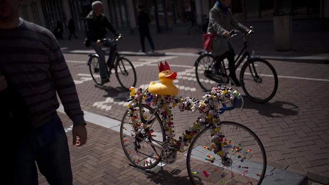 Cyclists ride past a bicycle decorated with dozens of plastic ducks in downtown Amsterdam, Netherlands Sunday, April 28, 2013. Queen Beatrix has announced she will relinquish the crown on April 30, 2013, after 33 years of reign, leaving the monarchy to her son Crown Prince Willem Alexander. (AP Photo/Emilio Morenatti)