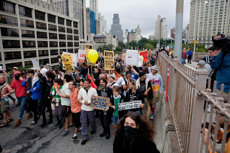 A large group of protesters affiliated with the Occupy Wall Street movement march across the Brooklyn Bridge, effectively shutting parts of it down, Saturday, Oct. 1, 2011 in New York. Police arrested dozens while trying to clear the road and reopen for traffic.(AP Photo/Will Stevens)