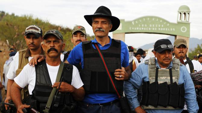 Jose Manuel Mireles, head of Michoacan state's community police, stands with vigilantes in Churumuco