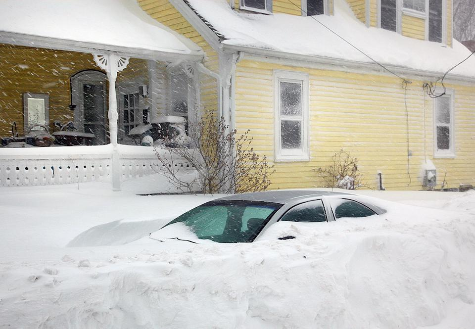 A car is nearly submerged in a snow bank in Hull, Mass., Tuesday, Jan. 27, 2015. Massachusetts was pounded by snow and lashed by strong winds early...