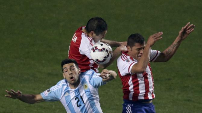 Argentina's Pastore jumps to head the ball with Paraguay's Aguilar and Ortiz during their Copa America 2015 semi-final soccer match at Estadio Municipal Alcaldesa Ester Roa Rebolledo in Concepcion