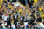 Norwich City's Scottish striker Robert Snodgrass (R) celebrates his equalizing goal with supporters during their English Premier League football match against Tottenham Hotspur at White Hart Lane in north London
