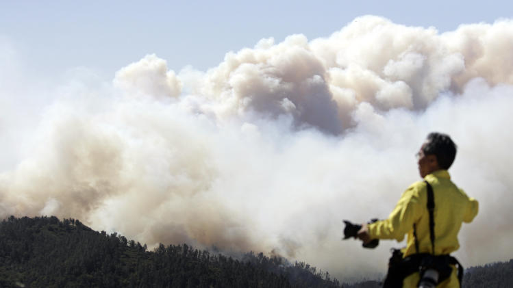 FILE - In this May 2008 file photo showing San Jose Mercury News photographer Gary Reyes photographing a wildfire in the Santa Cruz Mountains in Santa Cruz County, Calif. Colorado has some of the tightest restrictions on news media coverage of wildfires, keeping reporters miles away from burn areas and erecting barriers to access to officials in the know and as well as victims. California, by contrast, allows media reporting on active wildfires inside the wildfire zones, at reporters' own risk. (AP Photo/Paul /Sakuma,File)