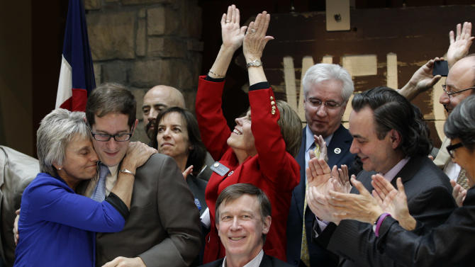Rep. Joann Ginal, left, hugs Rep. Mark Ferrandino, after Colorado Gov. John Hickenlooper, seated center, signed the Civil Unions Act into law at the Colorado History Museum in Denver, Colo., on Thursday, March 21, 2013. (AP Photo/Brennan Linsley)