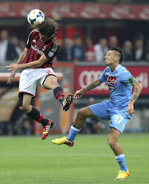 AC Milan midfielder Andrea Poli, left, jumps to head the ball as Napoli midfielder Marek Hamsik, of Slovakia, looks at him during the Serie A soccer match between AC Milan and Napoli at the San Siro s