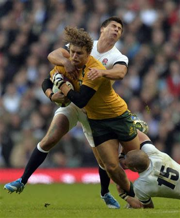 England's Youngs and Brown tackle Australia's Cummins during their international rugby union test match in London
