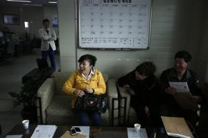 Gao reacts as she talks with a driving instructor at a driving school in Siheung