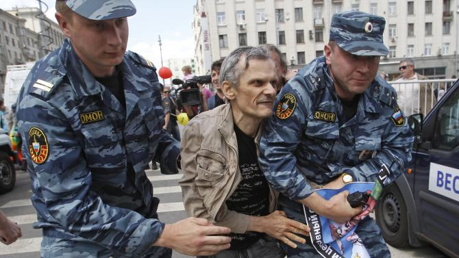 Russian police officers detain a gay rights activist during an attempt to hold a gay pride parade in Moscow, Russia, Sunday, May 27, 2012.  (AP Photo/Mikhail Metzel)