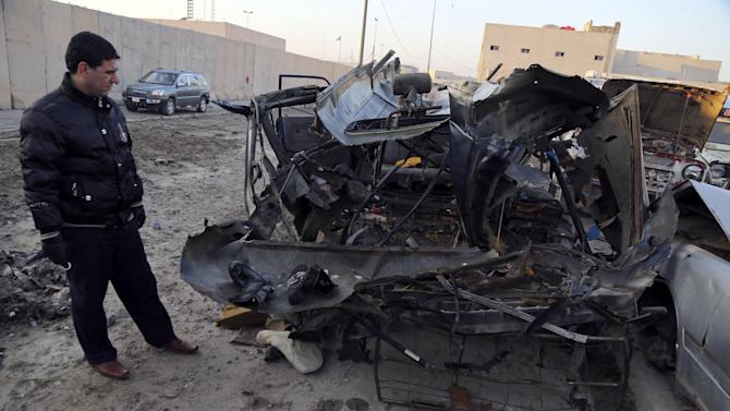 An Iraqi man inspects vehicles damaged in a car bomb attack in Baghdad, Iraq, Monday, Dec. 16, 2013. Iraqi officials say bombings in and around Baghdad have killed and wounded tens of people. (AP Photo/Karim Kadim)