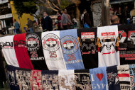 "T-shirts for sale are displayed in Tahrir Square, Cairo, Egypt, Thursday, Dec. 1, 2011. Judges overseeing the vote count in Egypt's first parliamentary elections since Hosni Mubarak's ouster say near-final results show Islamist parities taking a majority of seats contested in the first round. The Arabic writing on T-shirts read, ""Jan. 25, Revolution, freedom."" (AP Photo/Bernat Armangue)"